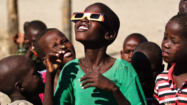 Kenyan school children look up at eclipse through special glasses