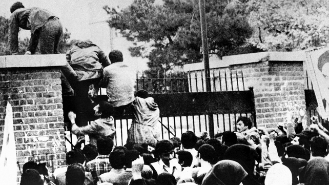 Iranian students climb over the wall of the US embassy in Tehran during the Iranian Revolution