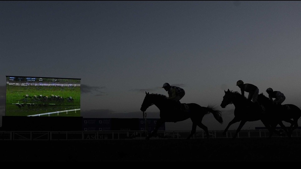 Runners make their way past the big screen in front of the grandstands at Ascot racecourse
