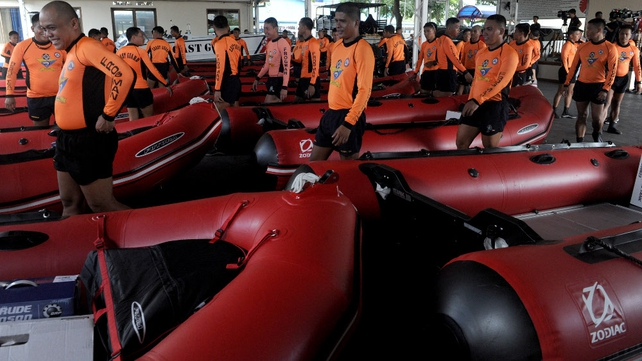 Philippine Coast Guard personnel stand in formation beside newly-acquired rubber boats following a blessing ceremony in Manila