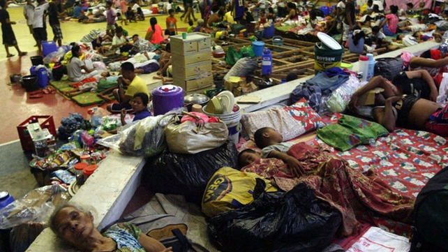 Residents sleep on the floor as they seek refuge inside a gymnasium turned into an evacuation center in Sorsogon City