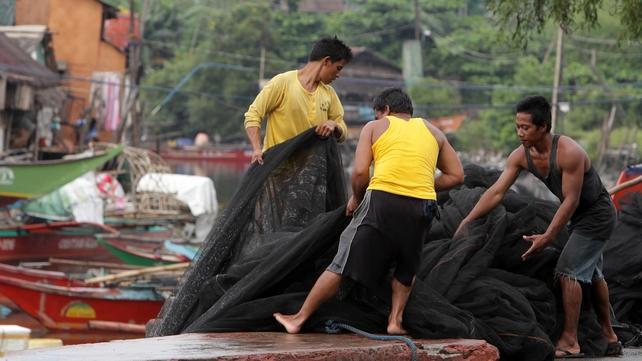 Filipino fishermen secure a net at a coastal village in Las Pinas city, south of Manila