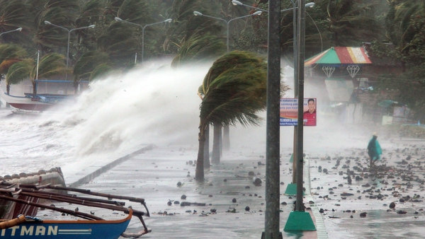 A resident walks past high waves pounding the sea wall in strong winds in the city of Legaspi, south of Manila