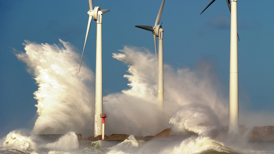 Waves break on a jetty holding wind turbines in the port of Boulogne-sur-mer, France