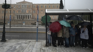 People stand at a bus stop to protect themselves from the rain in front of the Greek Parliament in Athens