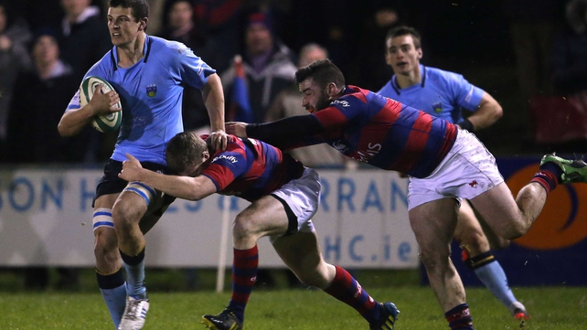 Clontarf's David Joyce and Michael McGrath tackle Eoin Joyce of UCD