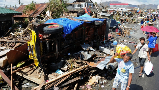 Residents walk past debris and an overturned jeepney in Tacloban City