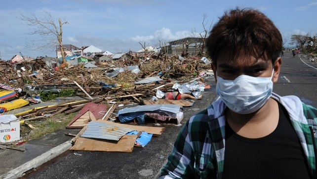 A resident covers his face with a mask as he rides past dead bodies littered along a road in Tacloban