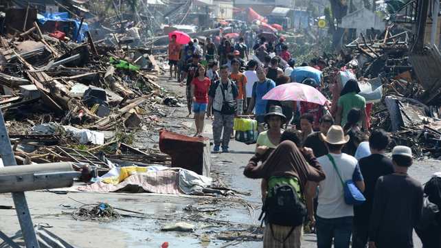 Residents walk through debris and victim's bodies in Tacloban City, Leyte province