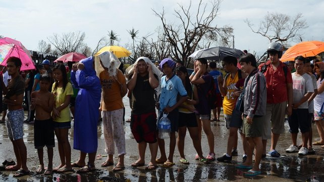 Affected residents wait in line for relief goods at a heavily damaged airport in Tacloban City, Leyte, Philippines