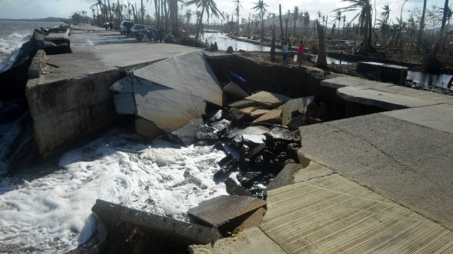 Residents cross a collapsed highway caused by the storm surge in Palo, eastern island of Leyte