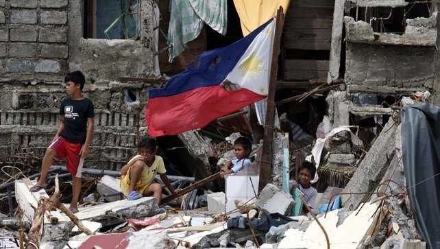 Filipino children stand in the rubble of houses in the devastated town of Hernani, Eastern Samar province
