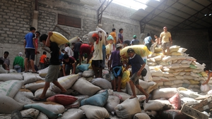Residents loot water damaged sacks of rice from a warehouse in Tacloban