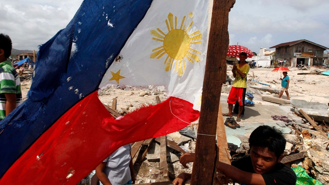 Children are seen next to a worn out Philippine flag in Hernani