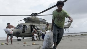 Survivors at the coastal village of Capiz carry sacks containing relief goods delivered via helicopter by the Armed Forces of the Philippines