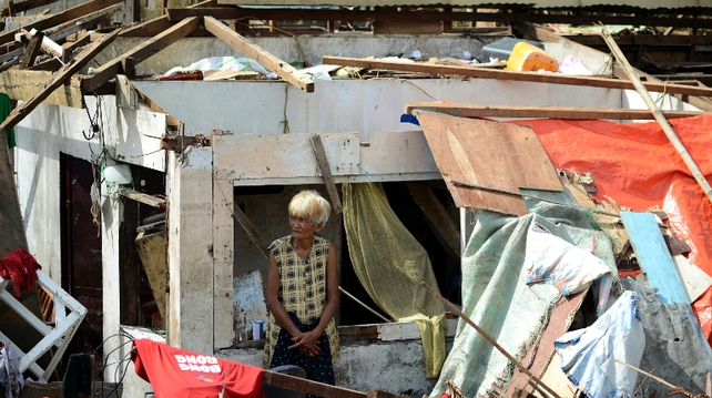 Woman surveys damage to her home