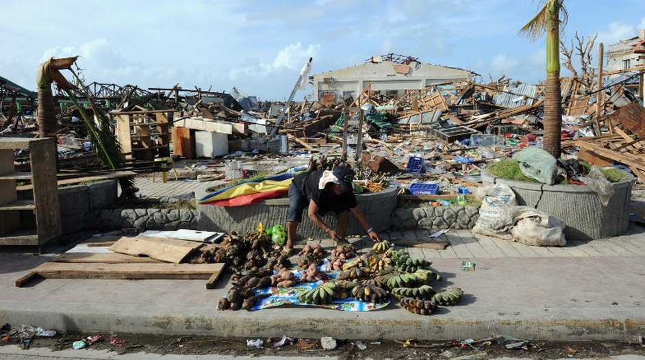 A fruit seller sets up a stall beside a ruined fruit market in the Philippines