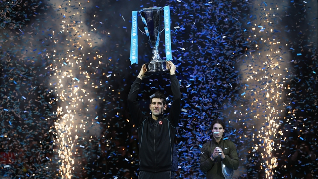 A disconsolate Rafael Nadal looks on as Novak Djokovic holds aloft the Brad Drewett Trophy