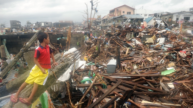 A young boy views the destruction in Tacloban, which bore the brunt of the typhoon