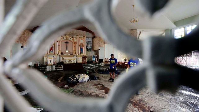 Filipino workers retrieve bodies of typhoon victims inside a church in Tacloban
