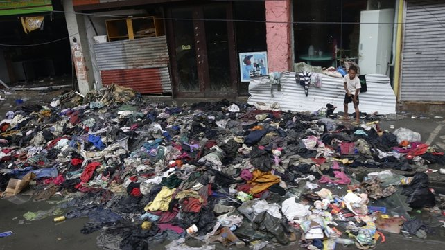 A boy sifts through clothes strewn on the streets of Tacloban