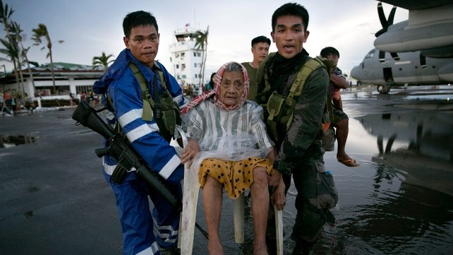 An elderly woman is carried to a waiting C130 aircraft during the evacuation of hundreds of survivors of Typhoon Haiyan
