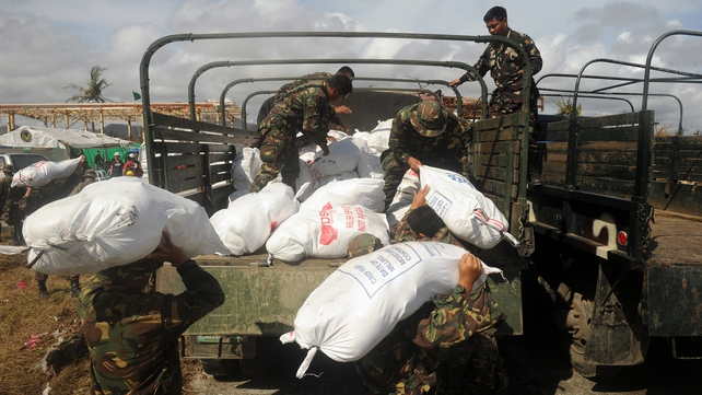 Soldiers load relief goods to a truck in Tacloban