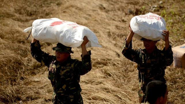 Philippine soldiers carry relief goods to be given to typhoon survivors in Tacloban