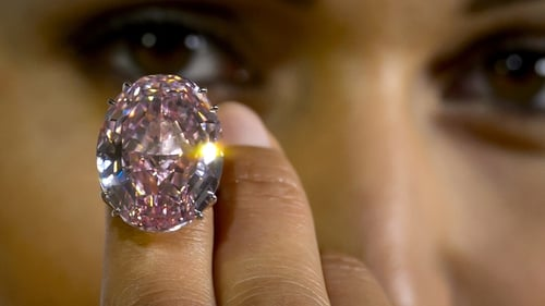A model displays 'The Pink Star', a 59.60-carat oval cut pink diamond