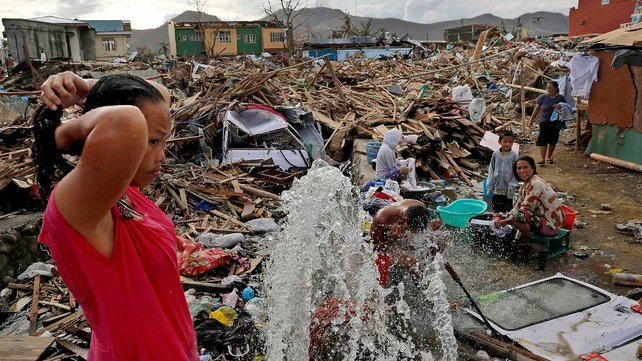 A woman washes amid scenes of devastation in the aftermath of Typhoon Haiyan