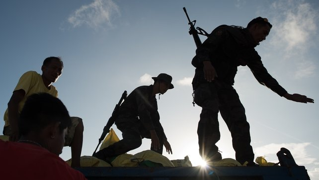 Local soldiers and workers load an army truck with bags of rice to be distributed to typhoon survivors, at Tacloban airport