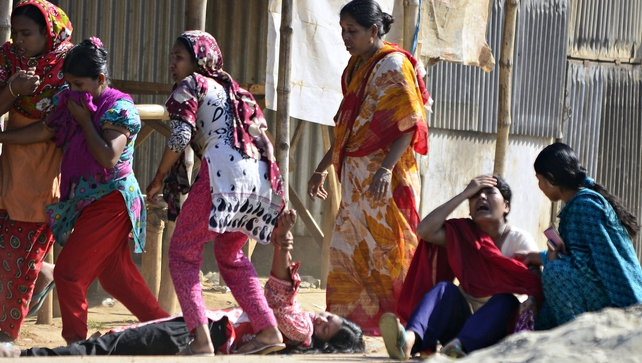Bangladeshi garment workers on the ground as others react after riot police fired tear gas shells during clashes in Ashulia
