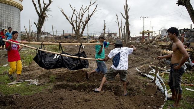 Relatives of typhoon victim Cristile Cahutay (22) who was swept out to sea carry her body to a grave in Palo