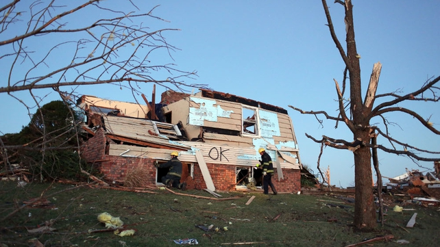 Firefighters search a heavily damaged home in Washington, Illinois