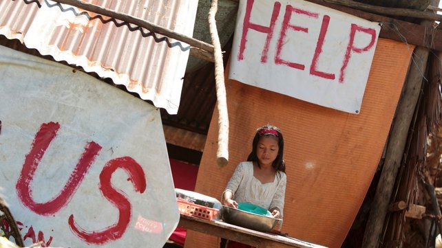 A young girl stands outside her damaged home in Leyte province