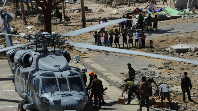 US and Philippine military personnel unload relief food from a US Navy Seahawk helicopter in the town of Hernani, Eastern Samar