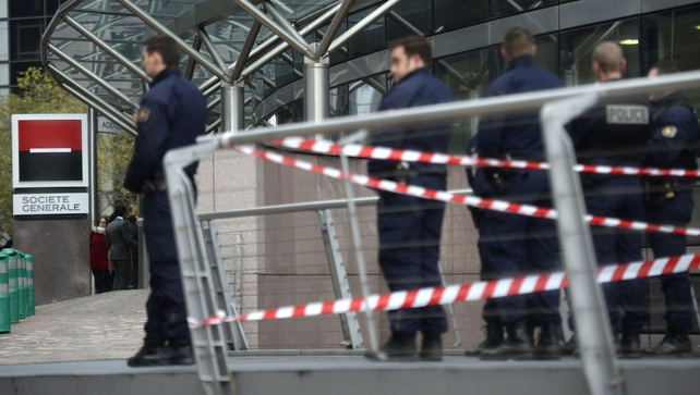 Police stand outside the entrance of the headquarters of the Societe Generale bank in the La Defense business district