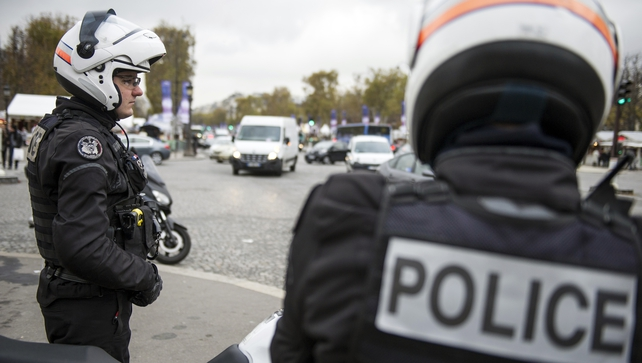Police officers patrol Champs-Elysees Avenue as efforts continue to trace the gunman