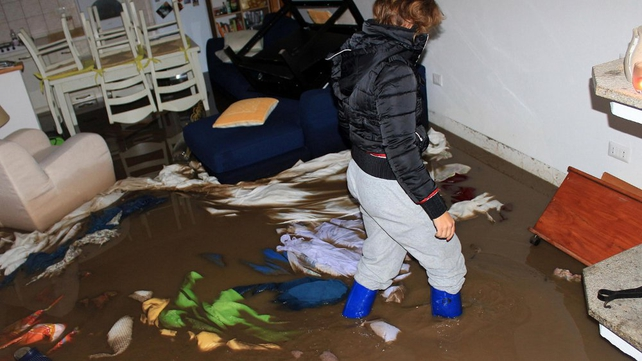 A woman wades through her flooded home in Olbia