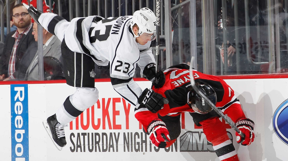 Mark Fayne (r) of the New Jersey Devils sends Dustin Brown of the Los Angeles Kings flying on a check during an NHL hockey game in Newark, New Jersey