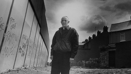 Father Alec Reid by one of Belfast's peace walls