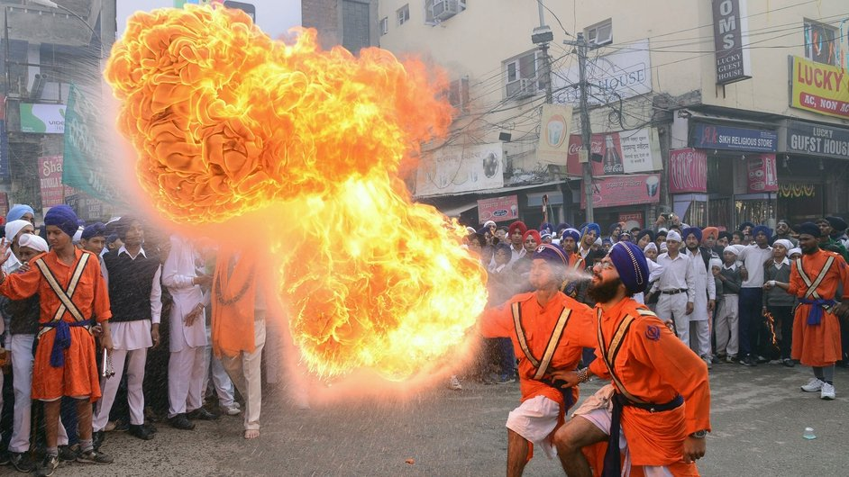 Indian Sikh Nihang warriors perform a fire breathing act during a procession from Sri Akal Takhat to the Golden Temple in Amritsar
