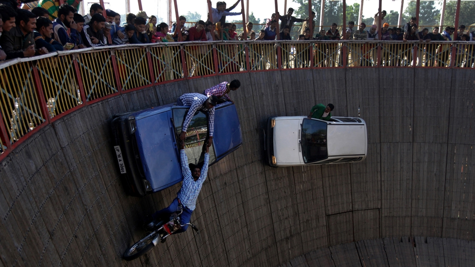 Performers ride cars and motor bikes inside a makeshift 'Wall of Death' in India