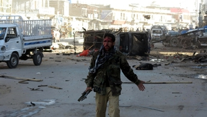 An injured Pakistani Frontier Corps officer stands at the scene of a bomb blast in Quetta