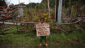 A child holds a placard asking for help by the side of the coastal road in Eastern Samar