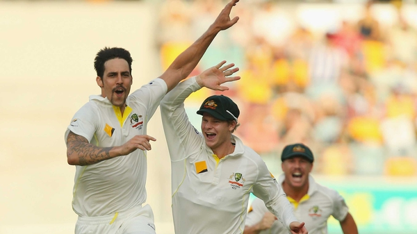 Mitchell Johnson of Australia celebrates with team mates Steve Smith (L) and David Warner after dismissing Jonathan Trott