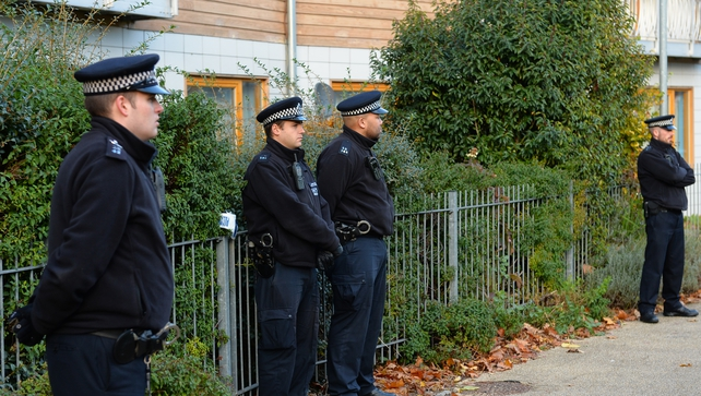 Police stand guard outside a block of flats in south London