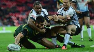 Darius Boyd of Australia scores a try through the tackle of Aaron Groom and Apisai Koroisau of Fiji