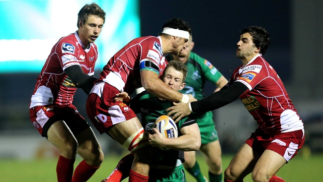Connacht's Matt Healy is tackled by Sione Timani and Gareth Owen of Scarlets