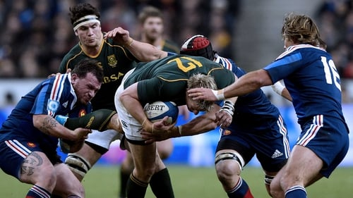 South Africa captain Jean de Villiers is tackled by Nicolas Mas (left) and  Dimitri Szarzewski (right) of France